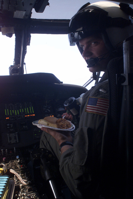 A pilot from Helicopter Antisubmarine Squadron Light 37 (HSL-37) takes a moment to get some chow provided by the ships galley off the USS REUBEN JAMES (FFG 57) while in flight off the coast of Peru. Due to mission requirements, he and his crew have been flying training exercises throughout the day and have had no opportunity to take a lunch break. The ship and crew are en route to Exercise TEAMWORK SOUTH '99. Reuben James will be conducting bilateral operations with the Chilean navy