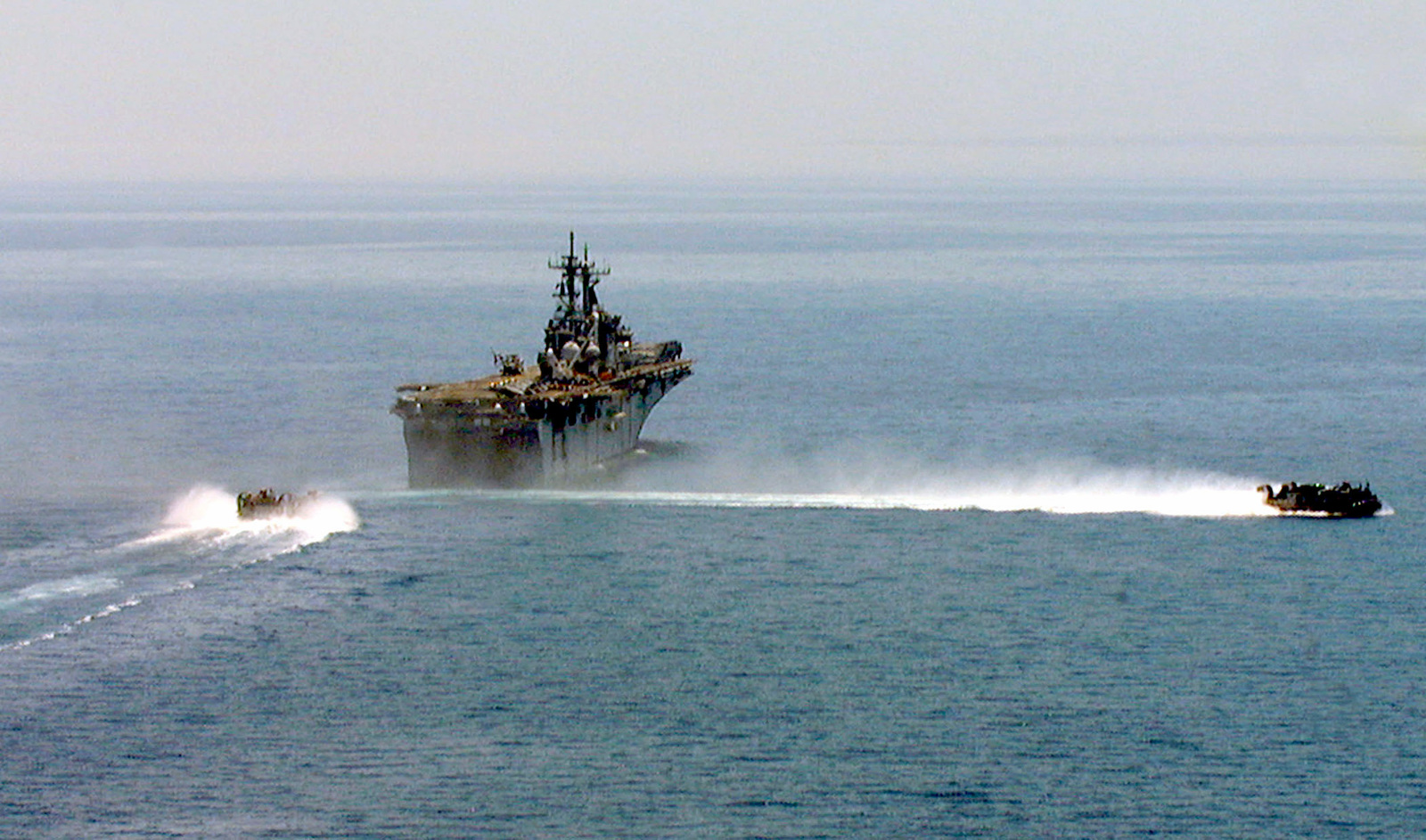 An Air Cushion Landing Craft (LCAC) leaves the well deck of the USS KEARSAGE (LHD 3) as another approaches to pick up more personnel and equipment from the 26th Marine Expeditionary Unit (MEU) and transport them to the beach at Litohoro, Greece. The first wave of Marines assigned to the 26th MEU arrived ashore in Litohoro during the early-morning hours in support of the NATO Peacekeeping Mission in Kosovo. The 26th MEU and USS KEARSAGE (LHD 3) Amphibious Ready Group are deployed in support of NATO Operation Allied Force