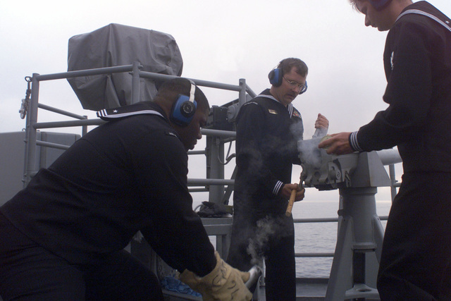 "US Navy GUNNER's Mate First Class Rupert Rose catches the spent ""saluting round"" shell casing as he and fellow crew aboard USS REUBEN JAMES (FFG-57) render a twenty-one gun salute while entering the port of Valparaiso, Chile. Reuben James will be participating in Exercise TEAMWORK SOUTH '99 in Chile"
