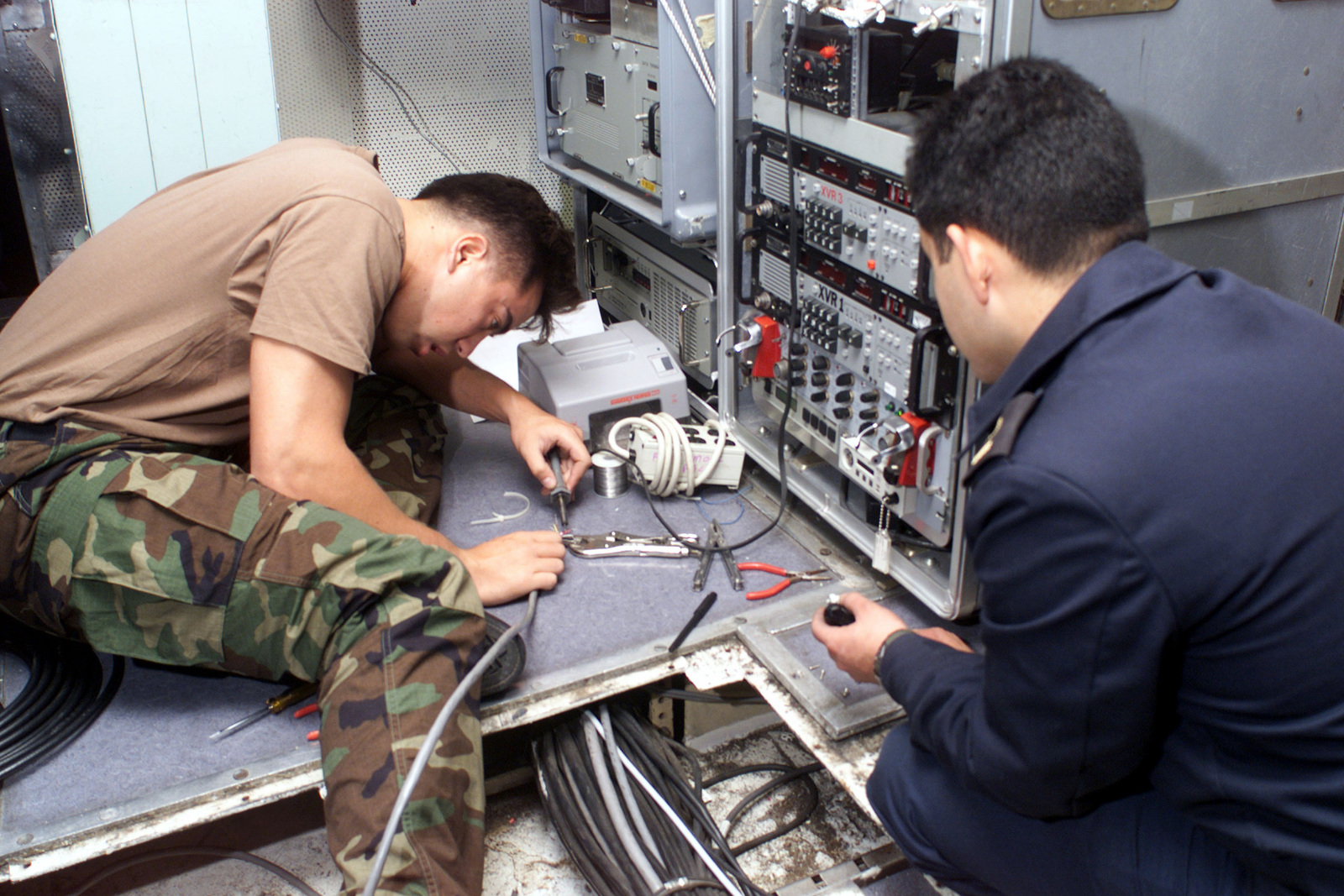 US Navy Electronics Technician 3rd Class James Kyne works with a Chilean sailor aboard the Chilean flagship BLANCO ENCALADA (DLH 15) in Valparaiso, Chile, installing a data link as part of Exercise TEAMWORK SOUTH '99. US, Canadian and Chilean forces will be working together on training exercises off the coast of South America through July