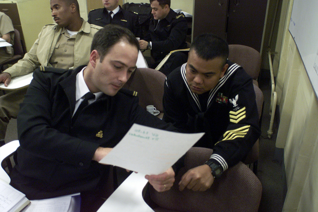 US Navy Radioman First Class Greg Viquelia, stationed aboard USS REUBEN JAMES (FFG 57), discusses communication issues with a Chilean officer aboard the Chilean flagship BLANCO ENCALADA (DLH 15) during an operations brief prior to Exercise TEAMWORK SOUTH '99 in Valparaiso, Chile