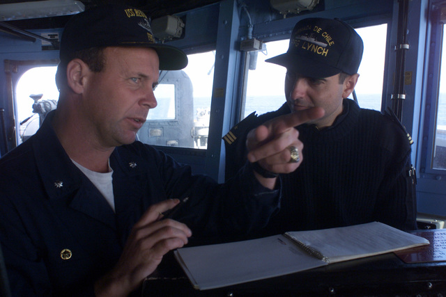 US Navy Commander Steven L Richter, Commanding Officer, USS REUBEN JAMES (FFG 57) discusses the correct translation in a note to be sent to the Commanding Officer of the Chilean replenishment oiler ARAUCANO (AO 53) (not shown) with Chilean Navy Lieutenant Claueio Carrasco during a training exercise on a light line transfer of packages between the two vessels underway as Exercise TEAMWORK SOUTH '99 starts