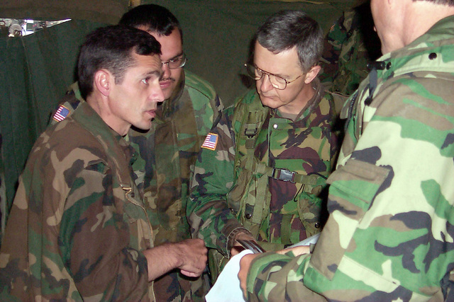 Brigadier General John Craddock, (Right), Commander, U.S. Kosovo Forces/Joint Task Force Falcon , listens to Colonel Ahmed Isusi, Commander, Karadak Zone of the Kosovo Liberation Army, near Cernica, Kosovo. The two leaders came together to sign a local agreement establishing a phased demobilization and demilitarization of KLA Forces in the U.S. Sector in support of NATO Operation Joint Guardian