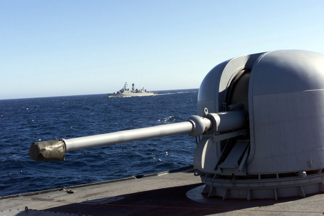 The Chilean flagship BLANCO ENCALADA (DLH 15) is framed by the 76mm gun mount from USS REUBEN JAMES (FFG 57) during Exercise TEAMWORK SOUTH '99 off the coast of Chile