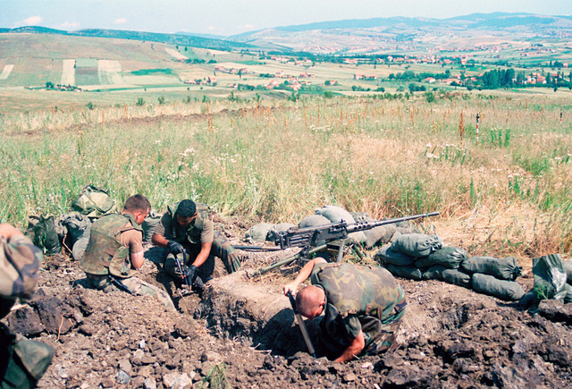 Marines from Lima Battery, 3rd Battalion, 10 Marine Regiment dig in after arriving at Camp Montieth near Cernica, Kosovo. This fighting hole is being dug around the M2 .50 caliber Browning machine gun. The Marines and sailors of the 26th Marine Expeditionary Unit (MEU) during Operation JOINT GUARDIAN are helping to enforce the implementation of the military technical agreement and to provide peace and stability to Kosovo