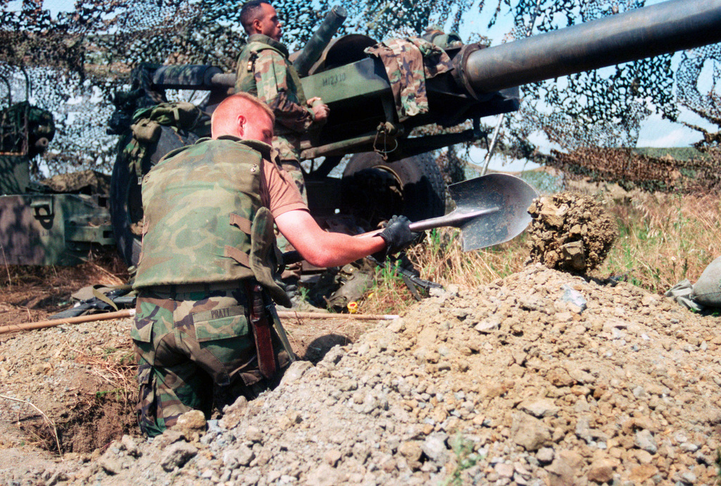 Marines from Lima Battery, 3rd Battalion, 10 Marine Regiment dig in next to an M198 155mm Medium Howitzer, Towed, after arriving at Camp Montieth near Cernica, Kosovo. The Marines and sailors of the 26th Marine Expeditionary Unit (MEU) during Operation JOINT GUARDIAN are helping to enforce the implementation of the military technical agreement and to provide peace and stability to Kosovo