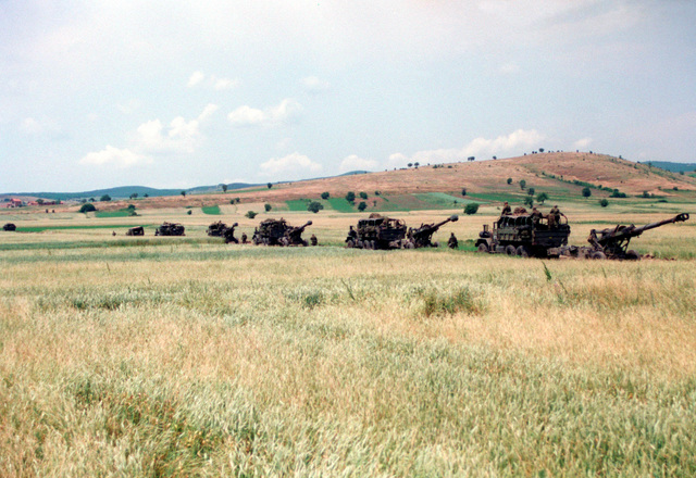 Marines from Lima Battery, 3rd Battalion, 10th Marine Regiment leave a staging area in Kosovo enroute to Camp Monteith, Forward Support Base, near Cernica, Kosovo. M198 155mm Medium Howitzers, Towed are attached to M813 Cargo trucks. The Marines and sailors of the 26th Marine Expeditionary Unit (MEU) during Operation JOINT GUARDIAN are helping to enforce the implementation of the military technical agreement and to provide peace and stability to Kosovo