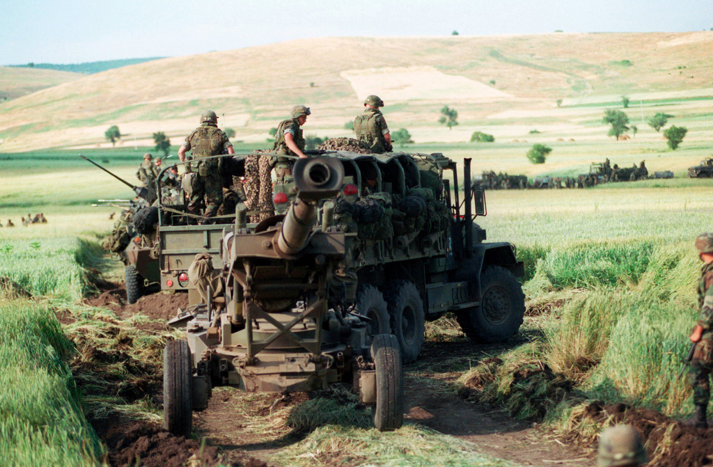 Marines from Lima Battery, 3rd Battalion, 10th Marine Regiment leave a staging area in Kosovo enroute to Camp Monteith, Forward Support Base, near Cernica, Kosovo. M198 155mm Medium Howitzer, Towed is pulled by M813 Cargo truck. The Marines and sailors of the 26th Marine Expeditionary Unit (MEU) during Operation JOINT GUARDIAN are helping to enforce the implementation of the military technical agreement and to provide peace and stability to Kosovo