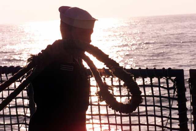The evening sun sets behind a sailor tending lines during sea-and-anchor detail aboard USS REUBEN JAMES (FFG 57) as the ship pulls in to Antofagasta, Chile, while participating in Exercise TEAMWORK SOUTH '99