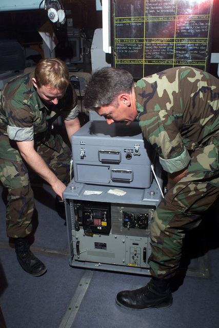 US Navy Operations SPECIALIST First Class Darrell Lafrentz, (left) and US Navy Electronics Technician First Class Michael McCoy (right), move communication equipment aboard the Chilean flagship BLANCO ENCALADA (DLH 15) in preparation for Exercise TEAMWORK SOUTH '99 while in the port city of Antofagasta, Chile