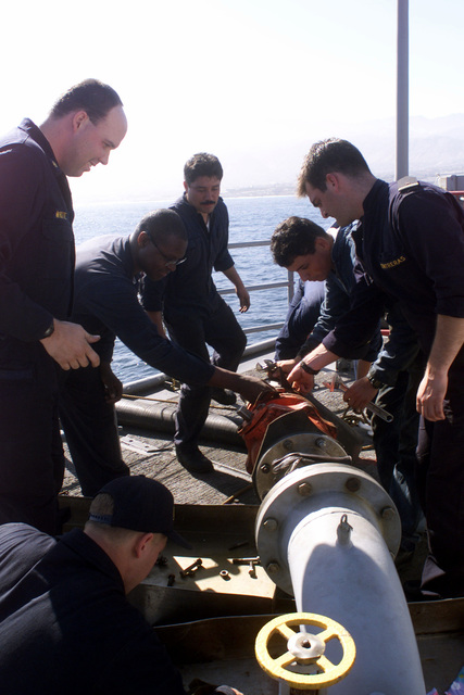 Crew members from USS REUBEN JAMES (FFG 57) and Chilean sailors work together to attach an adapter during refueling operations while anchored off the city of Antofagasta, Chile, during Exercise TEAMWORK SOUTH '99