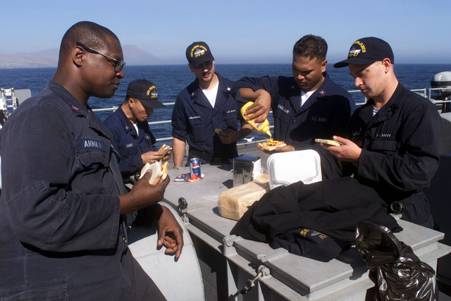 US Navy Gas Turbine Systems Technicians First Class Arnold, 3rd Class Yang, 3rd Class Adam Duranceau, 2nd Class Brad Marham and Fireman Johnson take a quick lunch break atop the 02 level aboard USS REUBEN JAMES (FFG 57) prior to re-fueling operations during participation in Exercise TEAMWORK SOUTH '99 off the coast of Antofagasta, Chile