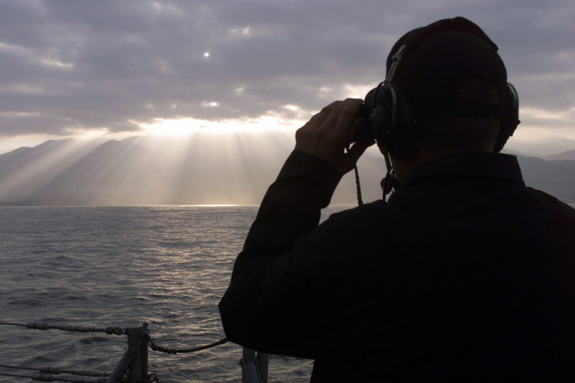 US Navy SEAMAN Sam Devaldo stands the aft look out aboard USS REUBEN JAMES (FFG 57) as the sun rises over the mountains of the port city of Antofagasta, Chile. His ship is getting underway to participate in the Exercise TEAMWORK SOUTH '99