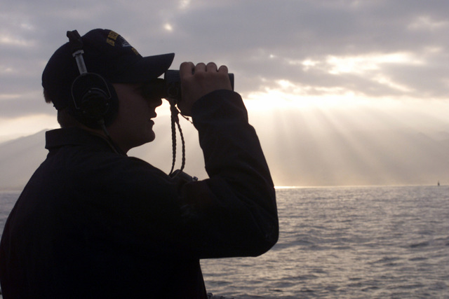 US Navy SEAMAN Sam Devaldo stands the aft look out aboard USS REUBEN JAMES (FFG 57) as the sun rises over the mountains of the port city of Antofagasta, Chile. His ship gets is getting underway to participate in Exercise TEAMWORK SOUTH '99