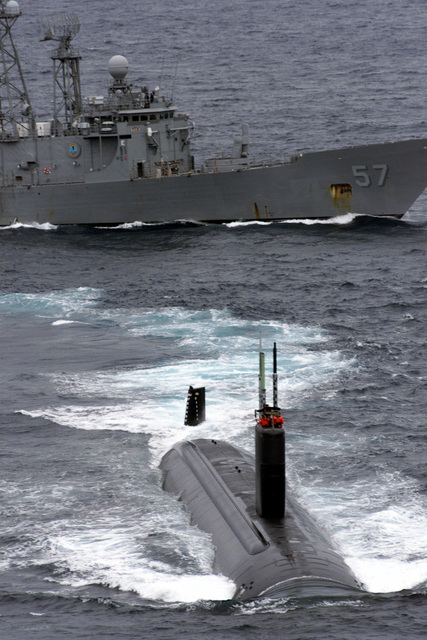 USS REUBEN JAMES (FFG 57) top and USS TUCSON (SSN 770) break formation during a photo exercise during Exercise TEAMWORK SOUTH '99 while off the coast of Chile