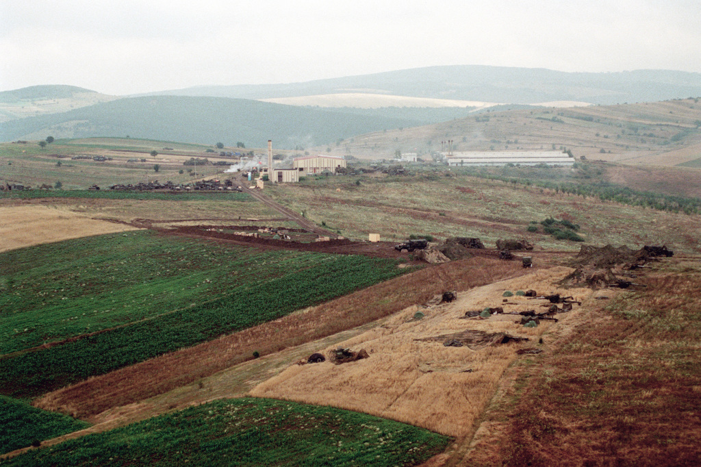Aerial view of MEU Service Support Group (MSSG)-26 Compound at Camp Montieth near Cernica, Kosovo. M198 155mm Medium Howitzers, Towed, can be seen in right foreground. The Marines and sailors of the 26th Marine Expeditionary Unit (MEU) are helping to enforce the implementation of the military technical agreement and to provide peace and stability to Kosovo during Operation JOINT GUARDIAN
