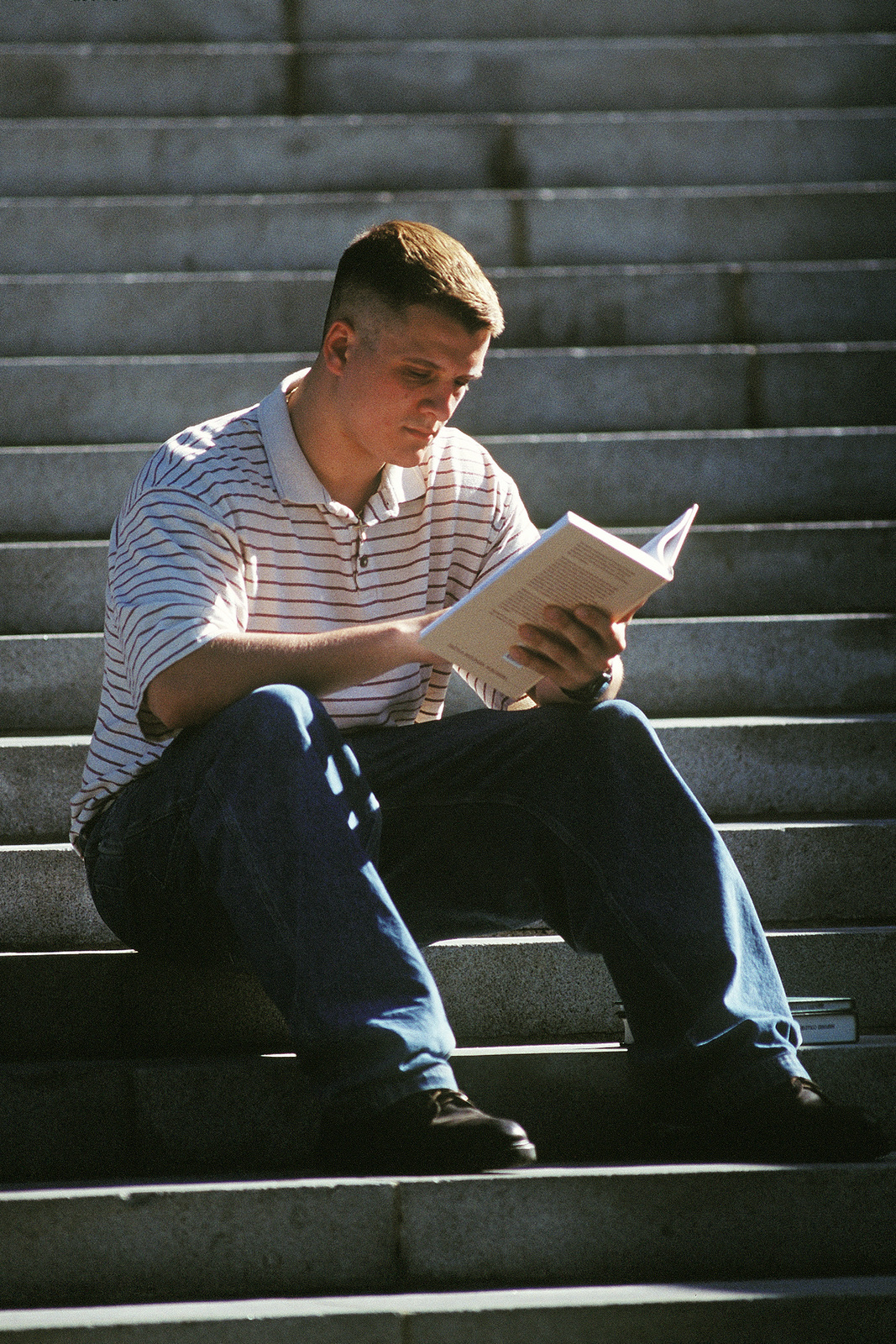 "Cadet Rob Caridad reads a textbook on the steps of Widener Library on the Harvard campus. Caridad is studying government at Harvard under an Air Force Scholorship program. Without the scholarship he would not have been able to attend the $35,000 a year institution. He reports to ROTC Detachment 365, Doolittle's Raiders, named after airpower pioneer and MIT alum General Jimmy Doolittle. Photograph used in the article ""Pillars of Education,"" from the August 1999 AIRMAN Magazine"