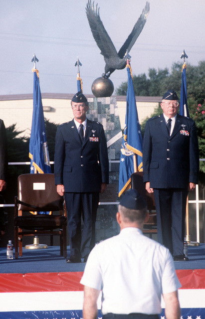 Brigadier General John Jernigan (left) and Brigadier General Lloyd Dodd (right) stand before the Sidney J. Brooks memorial and receive a report from Colonel David Lawrence, Commander of the 311th Contracting Office, acting as Group Commander, during the 311th Human Systems Wing Change of Command at Brooks Air Force Base, Texas