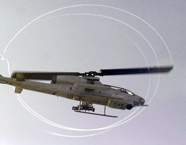 An AH-1W Super Cobra attack helicopter from Marine Medium Helicopter Squadron 365 (HMM-365), attached to the 26th Marine Expeditionary Unit (Special Operations Capable) (26th MEU(SOC)) as the ocean's mist creates streaks in the air around the helicopters rotor blades as it lifts off the USS KEARSARGE (LHD 3)