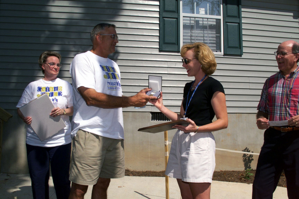US Army General Thomas A. Schwartz, Commanding General, Forces Command, presents the Commanders Award for Civilian Service to Beth Foley, Representative of the Habitat for Humanity International, as Charlie Gray, Resources Committee Chairman, Southern Crescent Habitat for Humanity, looks on during a Dedication Ceremony. The Dedication Ceremony is for the house that the US Army Association Foundation and The Department of Defense Community (Fort McPherson/Fort Gillem) sponsored through Habitat for Humanity, for Mrs. Anne Boddie of Trinity Park, Riverdale, Georgia