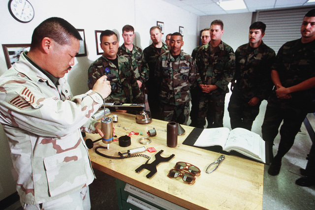 """US Air Force Technical Sergeant Ricky Hamada goes over safety devices and fuses. The soldiers are taking a basic course in bombs. This photograph was used in the article """"Bomb U."""", AIRMAN Magazine, September 1999 issue"""