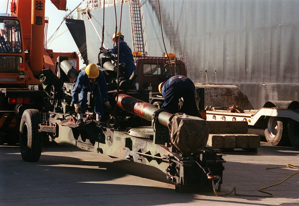 Japanese dock workers ready a USMC M198 155mm Howitzer to be lifted and set down on the back of a flat bed trailer at the Hamasaki Port, Hokkaido, Japan