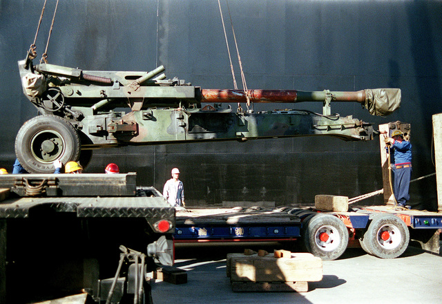 Japanese dock workers ready a USMC M198 155mm Howitzer to be set down on the back of a flat bed trailer at the Hamasaki Port, Hokkaido, Japan