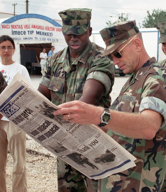 During Operation AVID RESPONSE (OAR) Marine Corps First Lieutenant Charles Lollar (left) points out photographs in a Turkish newspaper of Marines putting up tents, to Colonel Kenneth J. Glueck, Commanding Officer of the 26th Marine Expeditionary Unit (SPECIAL OPERATIONS CAPABLE) (MEU(SOC)) as they wait in the Red Crescent camp at Dogu Kisla, Turkey for the arrival of Secretary of State Madelaine Albright. OAR is the US European Command contribution to relief efforts following the earthquake that struck about 65 miles east of Istanbul near the town of Izmit. Turkish officials estimate about 600,000 people are homeless