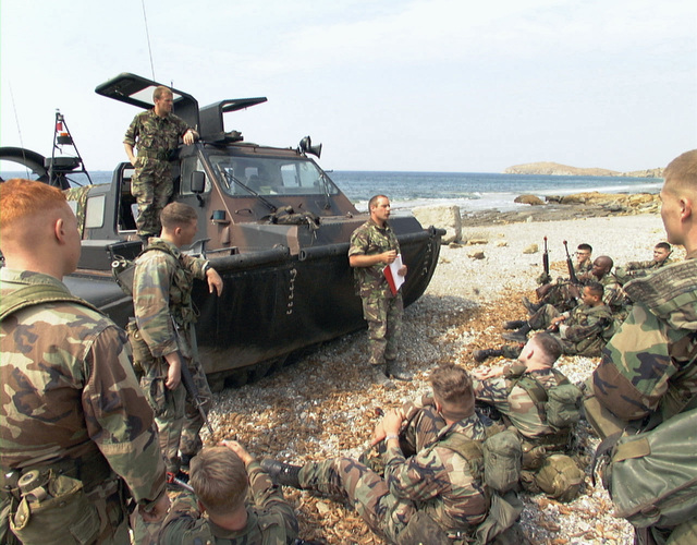 British Royal Marine Sergeant Nobby Hall, standing in front of a Landing Craft Air Cushioned (LCAC), from 539th Assault Squadron explains British assault procedures to United States Marines. Marines from the 26th Marine Expeditionary Unit (Special Operations Capable) (MEU(SOC)), embarked aboard the USS PONCE (LPD-15), are participating in the NATO exercise, NORTHERN APPROACH, with British and Turkish forces