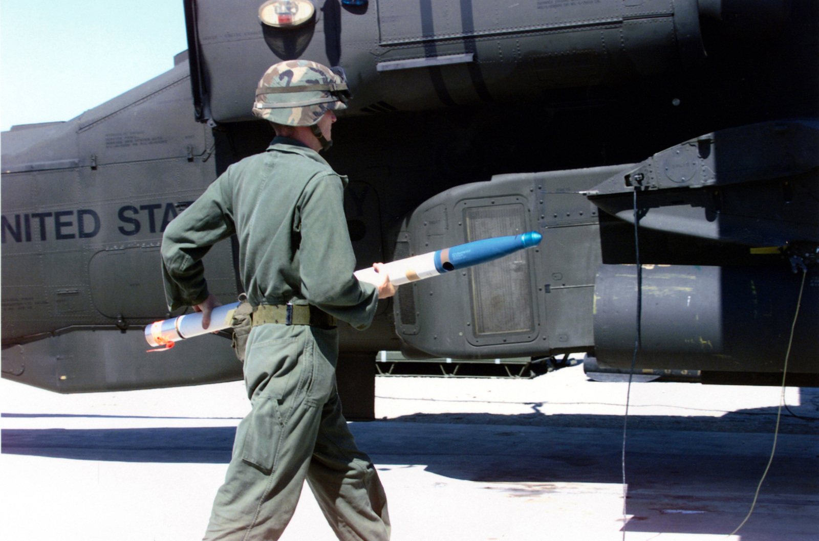 Sergeant John P. Green loads a 2.75 in FFAR (folding fin aerial rockets) into a AH-64D Apache Longbow Helicopter from the 1ST Battalion, 227th Aviation Regiment, First Cavalry Division during an annual aerial gunnery exercise. The helicopter landed at the Dalton/Henson Range Complex at Fort Hood, Texas. (Duplicate image, see also DDSD0108878 or search 990915A4980V049)