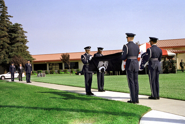 Medium long shot, the Travis Air Force Base, California, Elite Honor Guard perform a double flag folding ceremony during a special retreat ceremony held on 17 September 1999, honoring all POW/MIAs. Brigadier General Steven A. Roser, USAF, Commander 60th Air Mobility Wing, Travis AFB, and Major Robert Brubaker (U.S. Air Force Retired) are in left background. Not shown - BG Roser presented MAJ Brubaker with the Purple Heart