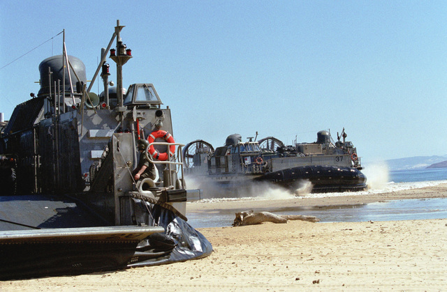 Air Cushion Landing Craft 37, right, moves onto the beach at Cap Serrat, Tunisia during Exercise ATLAS HINGE as LCAC 28 comes off cusion and lowers the ramp to offload Marines and vehicles from the 26th Marine Expeditionary Unit (SOC)