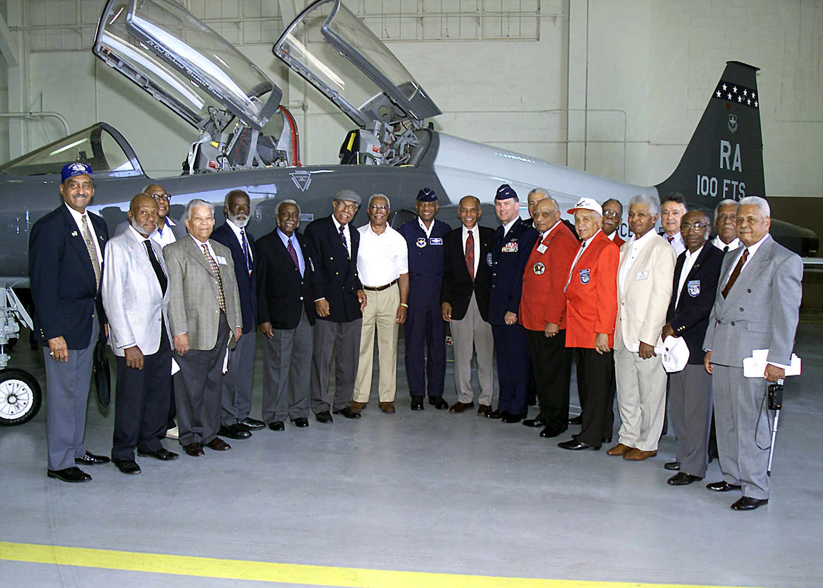 """Hangar interior, medium long shot, front view, General Lloyd W. """"Fig"""" Newton, USAF, Commander, Air Education and Training Command, Randolph Air Force Base, Texas, (center) stands with 16 Tuskegee airmen from the 100th Fighter Squadron, 340th Flying Training Group personnel and an unidentified USAF Major General in front of a T-38C Talon. The 100th FS was one of four all black units originally assigned to Tuskegee Army Air Base, Alabama. The World War II squadrons never lost a bomber under their escort to enemy fighters. Two Tuskegee Units the 99th and 100th FSs was reactivated as the 99th and 100th Flying Training Squadrons, 340th Flying Training Group, Air Force Reserve Command"""