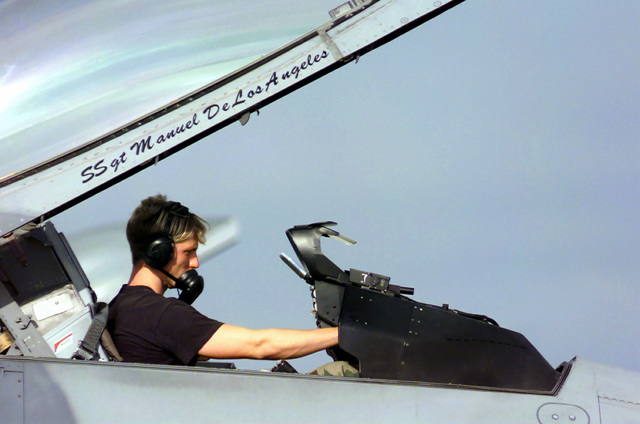 Right side profile, medium close-up shot as US Air Force SENIOR AIRMAN Ashley Buchanan, Weapons Technician with the 555th Fighter Squadron, Aviano Air Base, Italy, performs a weapons system check on a deployed F-16 Falcon at the MacDill Air Force Base, Florida, Deployed Unit Complex