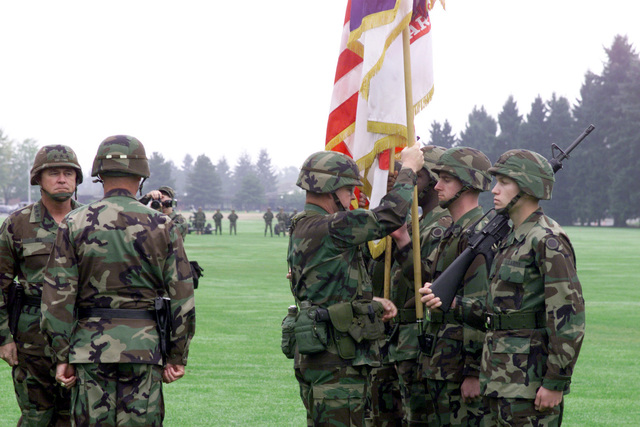 Command Sergeant Major Johnny J. Austin secures the colors following the exchange of command from Lieutenant General George A. Crocker, out-going commander to Lieutenant General James T. Hill, in-coming commander, during the I Corps and Fort Lewis Change of Command Ceremony on 30 September 1999 at Watkins Field, Fort Lewis, Washington. General Thomas A. Schwartz (left), Commanding General, Forces Command, was the Reviewing Officer