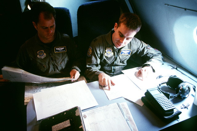 """US Air Force Captains Paul Frydenlund and Michael Drew, copilots of a C-5 Galaxy aircraft from the 349th Air Mobility Wing, Travis Air Force Base, California, review paperwork at 35,000 feet in the crew compartment. On board the aircraft is a US Navy Mark V special operations craft, a 50-ton, 82-foot-long speed boat (not shown) used to insert and extract SEAL combat swimmers in and out of high-threat areas. This long-Haul mission to Spain required an augmented crew, because of its duration and numerous legs. This photo is part of the article """"In a """"Galaxy' Far, Far Away"""" from the October 1999 issue of AIRMAN Magazine"""