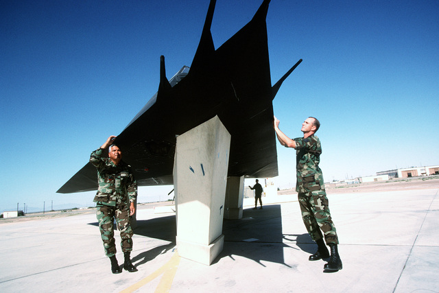 "US Air Force MASTER Sergeant Tony Garza (left) and STAFF SGT. Dan Jeffries prep an F-117 aircraft for a photo shoot with Holloman's Diagnostic Imaging Radar. Subtle flaws in the radar-absorbent coating can make a stealth aircraft appear on radar screens. The panels around the jet's landing gear also are coated with radar-absorbent material, so the aircraft's radar signature is the same as it would be in flight. This photograph is from the article ""Now you see it, Now You Don't,"" in the October 1999 issue of AIRMAN Magazine"