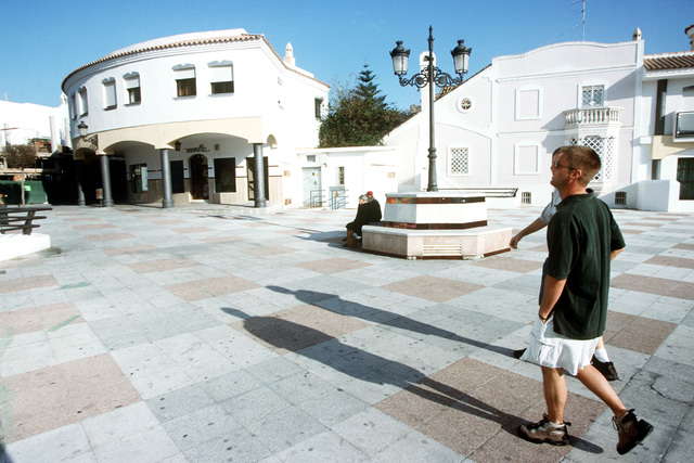 """US Air Force STAFF Sergeant Paul Jaspersohn and a fellow crew member stroll through a plaza in downtown Rota, a seaside resort in southern Spain. This photograph is part of the article """"In a """"Galaxy' Far, Far Away"""" from the October 1999 issue of AIRMAN Magazine"""