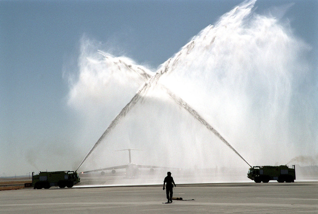Long shot, side view, two Travis Air Force Base, California, fire trucks create a welcome arch of water for a C-5 Galaxy taxiing toward camera in background. Not show - Piloting the C-5 for a last flight was Brigadier General Steven A. Roser, USAF, Commander, 60th Air Mobility Wing. BG Roser is retiring after 29 years in the United States Air Force