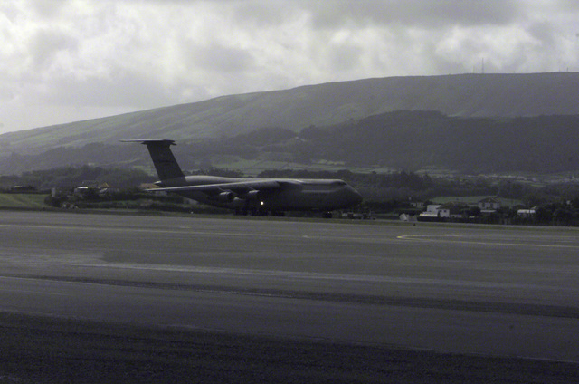 Right side profile long shot of a USAF C-5 Galaxy cargo aircraft as it rolls down the runway at Lajes Field, Azores, for take off. The C-5, from the 312th Airlift Squadron (AS), Travis AFB, California, is leaving Lajes Field for East Timor with several pallets of MRE's (Meals Ready to Eat). The MRE's are part of a joint US-Portugal humanitarian relief effort