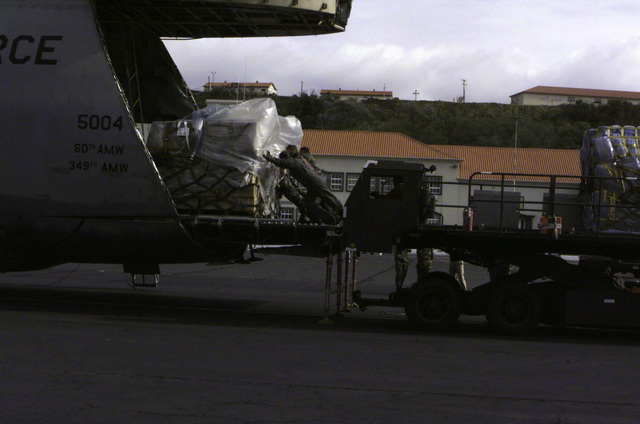 Right side profile medium shot of the open nose section on a USAF C-5 Galaxy cargo plane as members of the Portuguese Air Base 4 abd USAF members of the 629 AMSS (Air Mobility Support Squadron), Air Mobility Command, Lajes Field, Azores, move pallets of MRE's (Meals Ready to Eat) with a cargo loader onto the aircraft bound for East Timor. The C-5 Galaxy crew is from the 312th AS (Airlift Squadron), Travis Air Force Base, California. The MRE's are part of a joint US-Portugal humanitarian relief effort