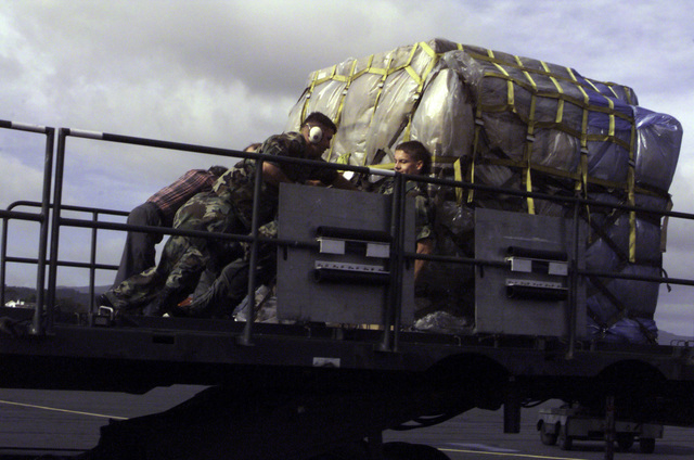 Right side rear view medium shot from a low angle up at members of the Portuguese Air Base 4 and USAF members of the 629th AMSS (Air Mobility Support Squadron), Air Mobility Command, Lajes Field, Azores, as they move pallets of MRE's (Meals Ready to Eat) off a cargo loader. The MRE's are part of a joint US-Portugal humanitarian relief effort