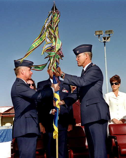 US AIr Force Colonel Thomas Kane (Right) takes hold of the 60th Air Mobility Wing guidon, presented by Lieutenant General John B. Sams of 15th Air Force at Travis Air Force Base, California, to show his acceptance as he takes the reigns and becomes the new wing commander at Travis AFB, Ca., on October 15, 1999. On the right is his wife, Renee, proudly watching. COL Kane is no stranger to Travis as he was once the former 86th Airlift Squadron (later changed to the 20th Airlift Squadron) Commander whose troops flew the C-141 Starlifter cargo aircraft. U.S. Air Force photo by Kristina P. Cilia