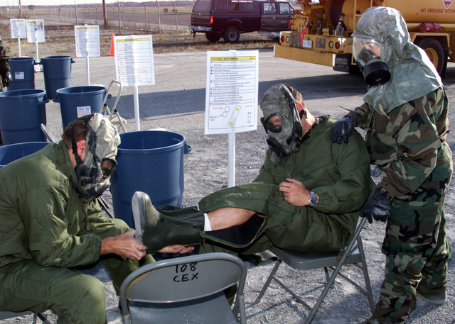A soldier (victim roll player) gets decontaminated after being under a Nuclear, Biological, Chemical (NBC) attack during a mock exercise. The soldier on the right has on the MCU-2/P series protective mask and is in Mission Oriented Protective Posture (MOPP) level 4. The other two personnel have on the M40 mask with the hood rolled up for ventilation and are in MOPP level 3 (gloves off)
