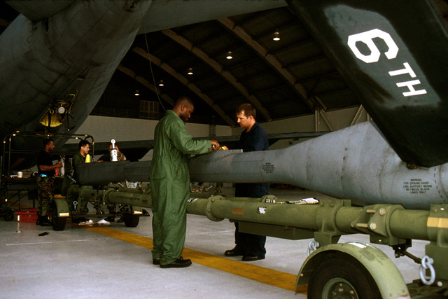 "A MacDill Air Force Base, Florida, maintenance crew prepares to reattach a refueling boom they overhauled to a KC-135 tanker. From left to right, are US Air Force STAFF Sergeants Davis Crisp, Rick Oftedahl, Tom Kinder, USAF SENIOR AIRMAN Nathaniel Roberson and USAF Technical Sergeant Steve Jacobs. This photograph is from the November 1999 AIRMAN Magazine article ""In the Right Place"""