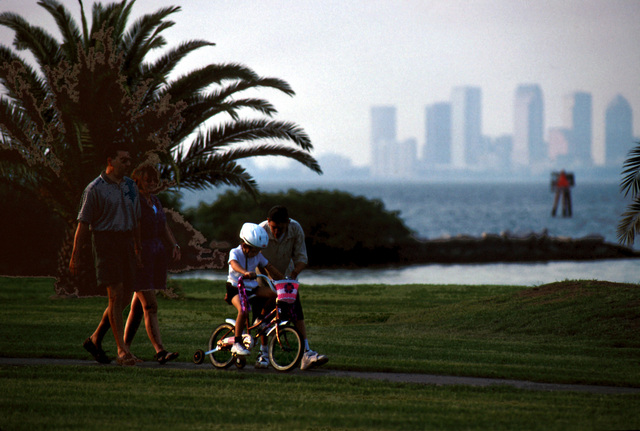 "With the Tampa skyline in the background, US Air Force MASTER Sergeant Alex Aceves and his wife, Starr, take a weekend stroll along MacDill's Bayshore Boulevard with their children, Alex, 14 and Danielle, 5. The base is working to retie bonds with the city of some 294,000 people. This photograph is part of the November 1999 AIRMAN Magazine article ""A Base Reborn"". (Substandard image)"