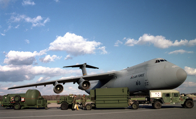 Medium shot.  Members of the 436th Communications Squadron show the size relationship of their new mobile radar unit in comparison to the C-5 Dover AFB, Delaware
