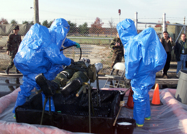 A soldier (victim roll player) gets decontaminated by civilians, in Hazmat (Hazardous Materials) gear, after being under a Nuclear, Biological, Chemical (NBC) attack during a mock exercise. The soldier is in Mission Oriented Protective Posture (MOPP) level 4