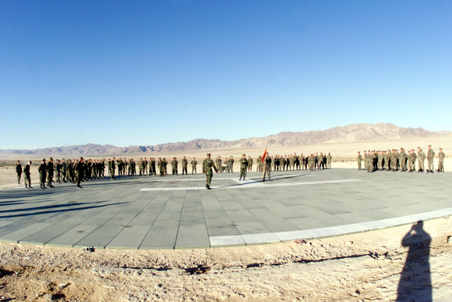 Straight on long shot with a wide angle, fish-eye lens at US Marines standing in formation on the Helicopter landing pad at Camp Wilson, Twentynine Palms Marine Corps Air-Ground Combat Center, California, during a celebration of the Marine Corps' 224th Birthday. The permanently and temporarily assigned Marines are taking part in Cax 2 (Combined Arms Exercise)