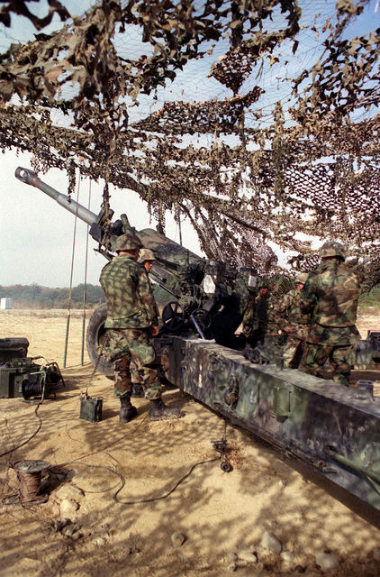 Left side rear view medium shot of a US Marine M198 155mm Howitzer as Marine Cannoneers from Lima Battery, 3rd Battalion, 12th Marines, from Camp Hansen, Okinawa, Japan, load an artillery round into the Howitzer. This training exercise took place at the Ojojihara, Japan range Artillery Relocation Shoot. (Portrait shot)